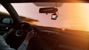 Woman driving a car on highway at sunset, with video recorder next to a rear view mirror